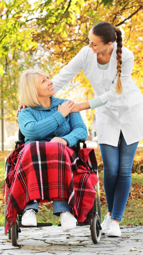 senior woman and young nurse in park