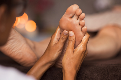 therapist hands doing foot massage at wellness center
