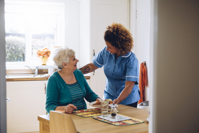 caregiver serving meal to a senior woman