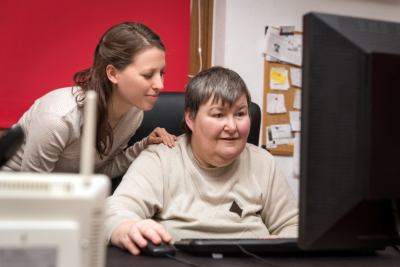 Caregiver and mentally disabled women learning at the computer, special education